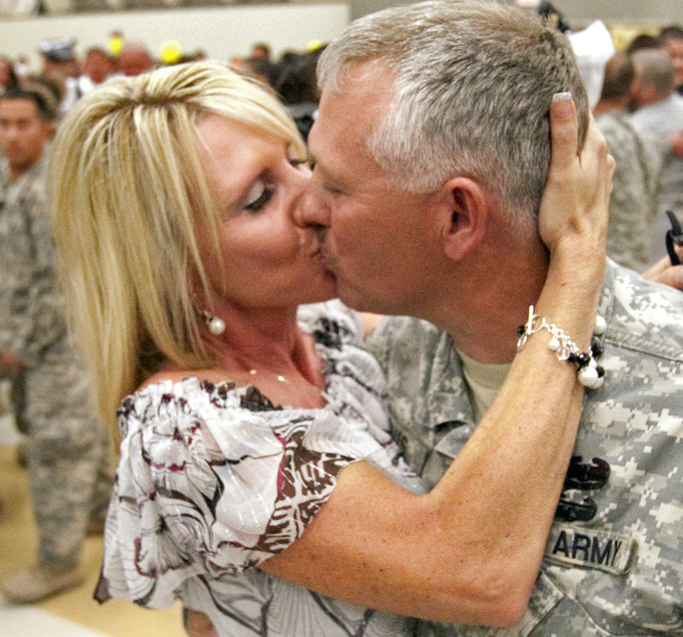 Wendy Davis kisses husband Danny as he and fellow soldiers from the 1-245th Airfield Operations Battalion return home on Tuesday, August 16, 2011, in Norman, Okla. after spending eight months in Afghanistan.