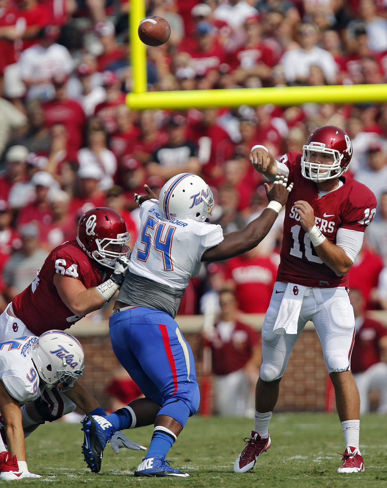 Photo - Oklahoma's Blake Bell (10) passes the ball over Tulsa 's Derrick Alexander (54) during the college football game between the University of Oklahoma Sooners (OU) and the University of Tulsa Hurricanes (TU) at the Gaylord-Family Oklahoma Memorial Stadium on Saturday, Sept. 14, 2013 in Norman, Okla.  Photo by Chris Landsberger, The Oklahoman