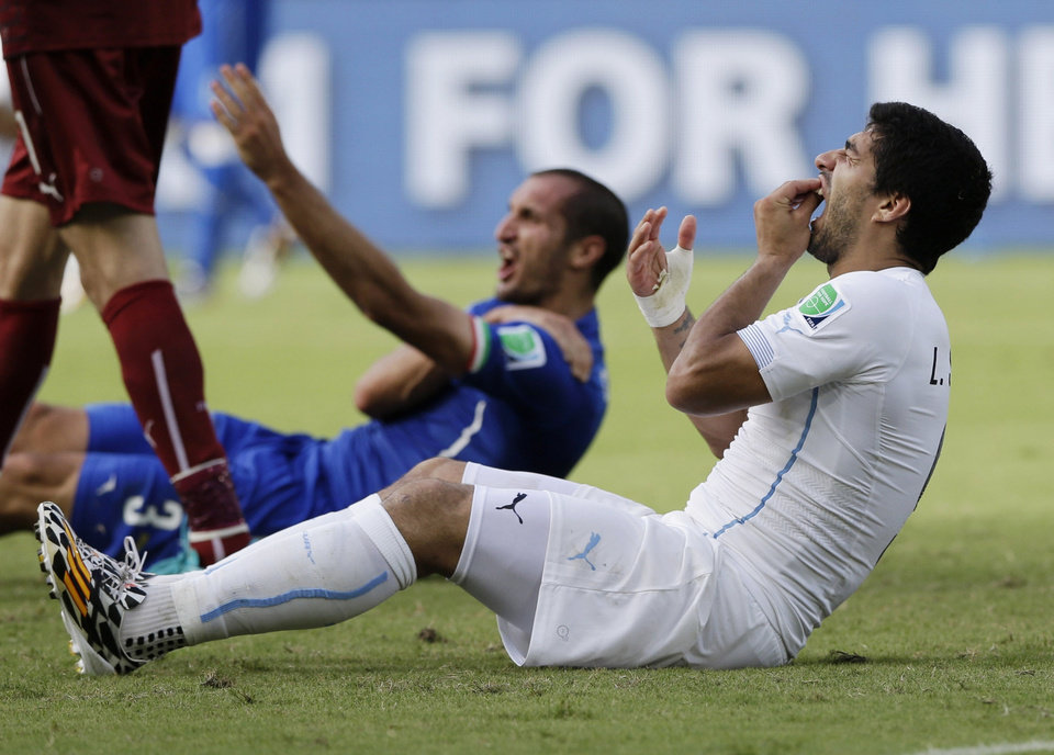 FILE - In this June 24, 2014 file photo, Uruguay's Luis Suarez holds his teeth after biting Italy's Giorgio Chiellini's shoulder during the group D World Cup soccer match between Italy and Uruguay at the Arena das Dunas in Natal, Brazil. On Thursday, June 26, 2014, FIFA banned Suarez for 9 games and 4 months for biting his opponent at the World Cup. (AP Photo/Ricardo Mazalan, File)