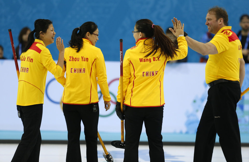 Photo - Team China coach Marcel Rocque of Canada congratulates his players, from left, Liu Yin, Zhou Yan and Wang Bingyu, on a good practice during the first day of curling training at the 2014 Winter Olympics, Saturday, Feb. 8, 2014, in Sochi, Russia. (AP Photo/Robert F. Bukaty)