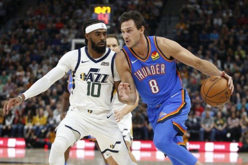 Photo -  Utah's Mike Conley, left, guards Oklahoma City's Danilo Gallinari  during the first half of Wednesday night's season opener in Salt Lake City. [AP Photo/Rick Bowmer]