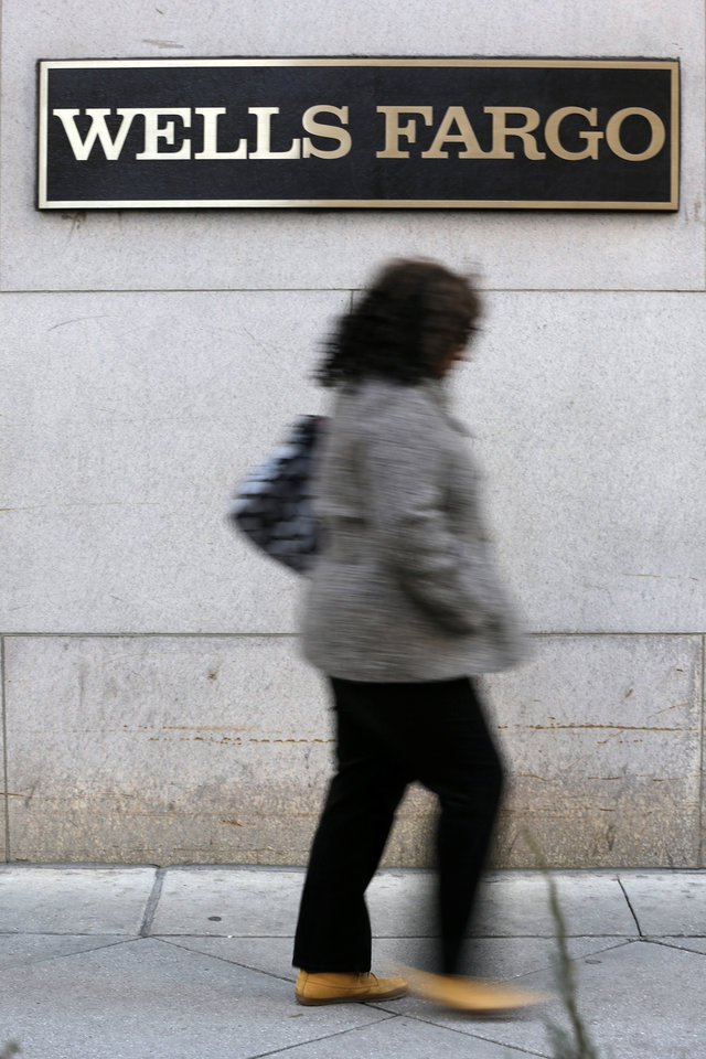 In this Wednesday, Dec. 19, 2012 photo, a woman walks past a Wells Fargo location in Philadelphia. U.S. banks are closing the year with the strongest profits since 2006 and fewer failures than at any time since the financial crisis struck in 2008. They're helping support an economy slowed by high unemployment, flat pay, sluggish manufacturing and anxious consumers. (AP Photo/Matt Rourke)