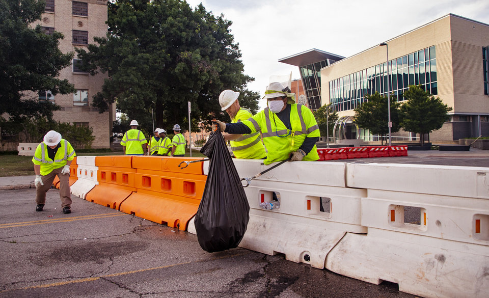 Photo - Crews clean up trash and damage from the George Floyd protest along Shartel Ave. on Monday, June 1, 2020, in Oklahoma City, Okla. [Chris Landsberger/The Oklahoman]