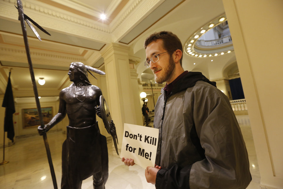 Photo - Sam Jennings with Oklahoma Coalition Against the Death Penalty holds a sign protesting the death penalty at the State Capitol in Oklahoma City, Tuesday April 29, 2014. Photo By Steve Gooch, The Oklahoman