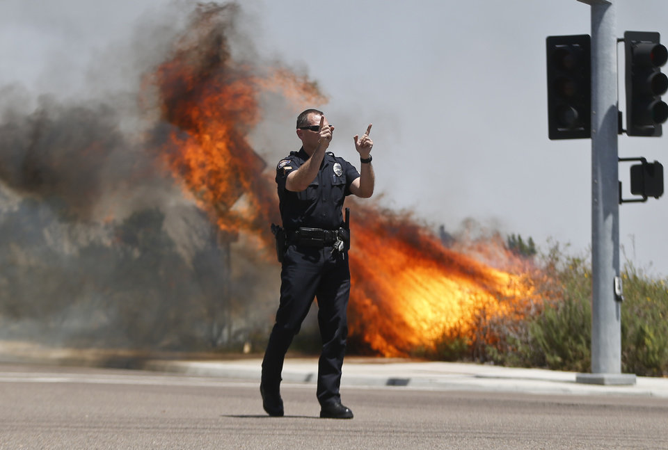 Photo - A Carlsbad,Calif. police officer turns traffic away as flames leap behind him Wednesday, May 14, 2014, in Carlsbad, Calif.  Weather conditions that at least temporarily calmed allowed firefighters to gain ground early Wednesday on a pair of wildfires that forced thousands of residents to leave their homes.  (AP Photo)