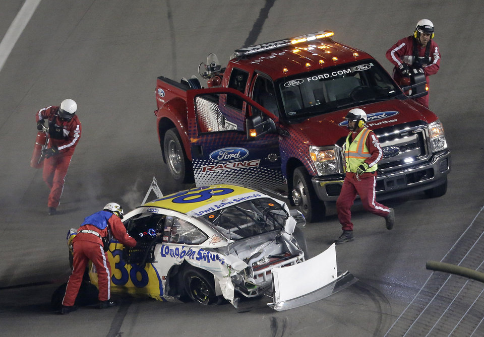 Photo - Rescue crews assist David Gilliland after he crashed during a NASCAR Sprint Cup Series auto race at Kansas Speedway in Kansas City, Kan., Saturday, May 10, 2014. (AP Photo/Charlie Riedel)