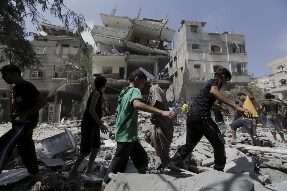 Photo - Palestinians walk on the rubble of a three-story building belonging to the Abdul Hadi family after an Israeli strike in Gaza City in the northern Gaza Strip, Sunday, Aug. 24, 2014. (AP Photo/Adel Hana)