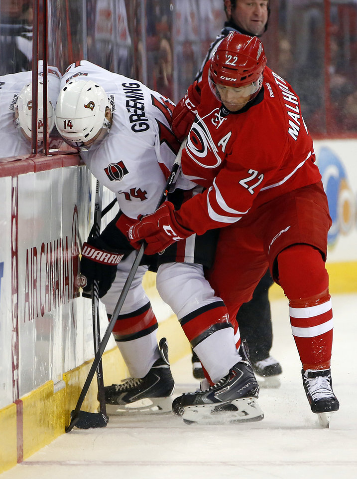Photo - Carolina Hurricanes' Manny Malhotra (22) and Ottawa Senators' Colin Greening (14) battle along the boards during the first period of an NHL hockey game in Raleigh, N.C., Saturday, Jan. 25, 2014. (AP Photo/Karl B DeBlaker)