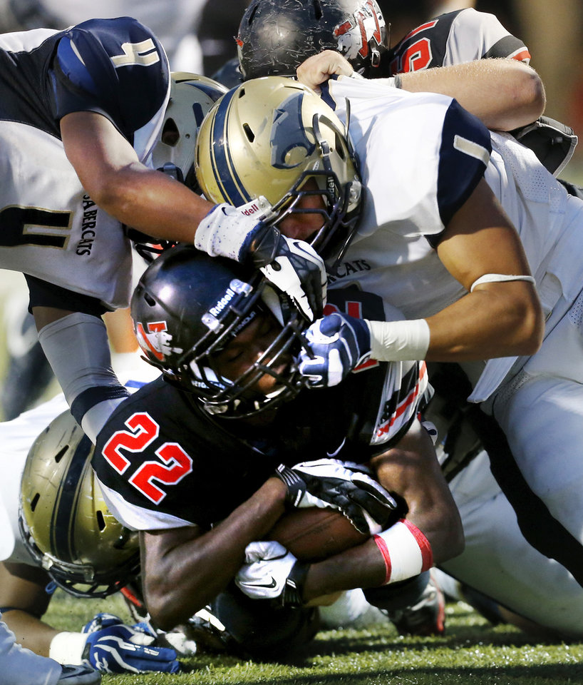 Photo - Westmoore's Austin Richards (22) is stopped short of the goal line by Southmoore's Nick Ward (1) and Johnathan Martin (4) as the Jaguars play the Sabercats in high school football on Friday, Sept. 7, 2012, in Moore, Okla.  Photo by Steve Sisney, The Oklahoman