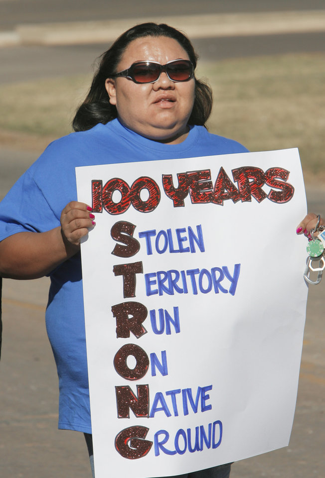 Photo - Shawndae Chaddlesone, a Kiowa, carries a sigh along the parade rout in Guthrie,  showing her displeasure with the centennial celebration, Friday, November 16, 2007.  By David McDaniel, The Oklahoman