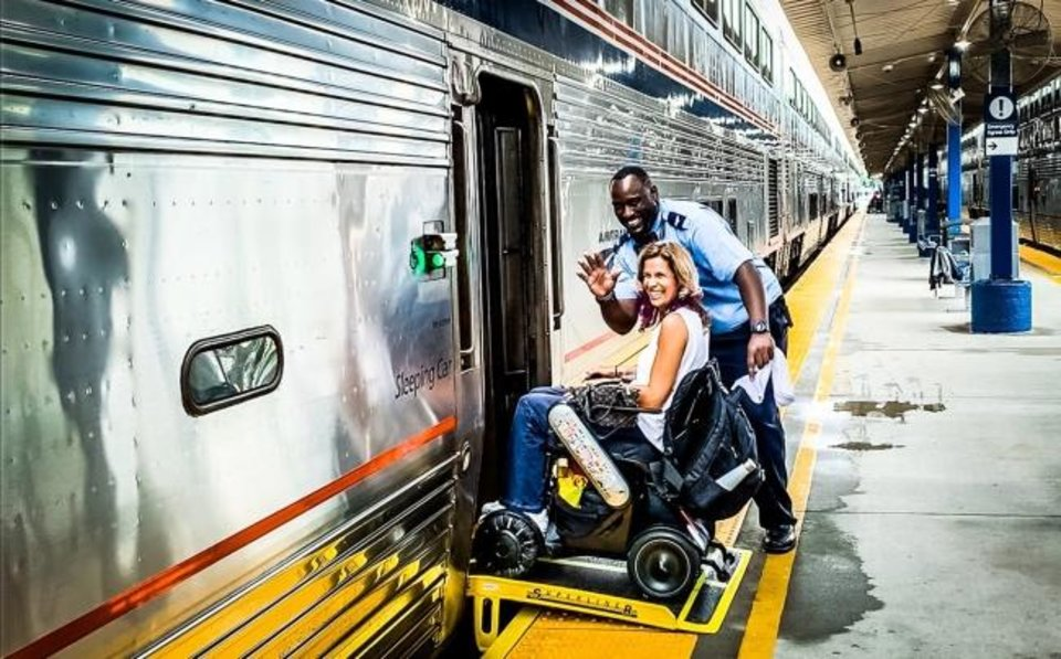 Photo -  Amtrak employee Chris Desper, aka Big Chris, helps Sylvia Longmire board the train in Sanford, Fla. [Sylvia Longmire]
