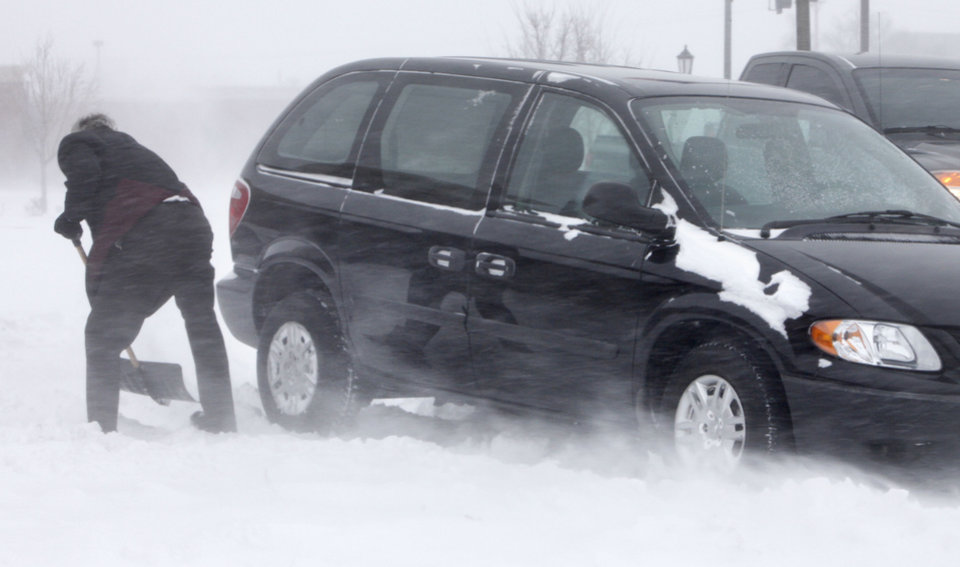A motorist uses a snow shovel to attempt to free his car which was stuck in drifting snow in downtown Edmond, OK, Tuesday, Feb. 1, 2011. By Paul Hellstern, The Oklahoman