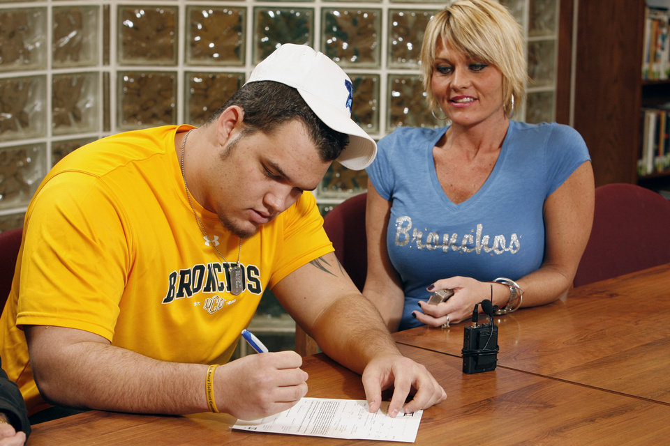 Photo - Cody Hughes signs a letter of intent to play college football while his mother Shawna watches at Norman North High School in  Norman, Okla. on Wednesday, Feb. 4, 2009.    Photo by Steve Sisney, The Oklahoman