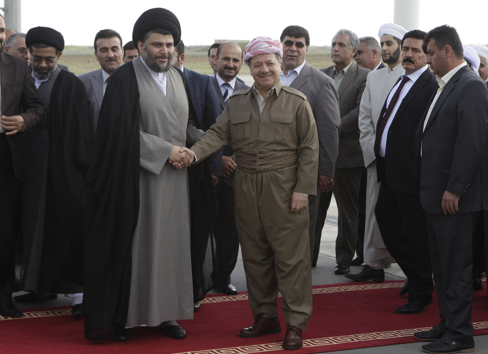 Photo -   Shiite cleric Muqtada al-Sadr, center left, shakes hands with Kurdish president Massoud Barzani, center right, upon his arrival in Irbil, a city in the Kurdish controlled north 217 miles (350 kilometers) north of Baghdad, Iraq, Thursday, April 26, 2012. A hardline Shiite cleric is meeting with the president of Iraq's Kurdish region to try to end a political crisis that has deadlocked the nation's government. Anti-American cleric Muqtada al-Sadr offered plans Thursday to resolve the impasse through political inclusiveness.(AP Photo/Khalid Mohammed)