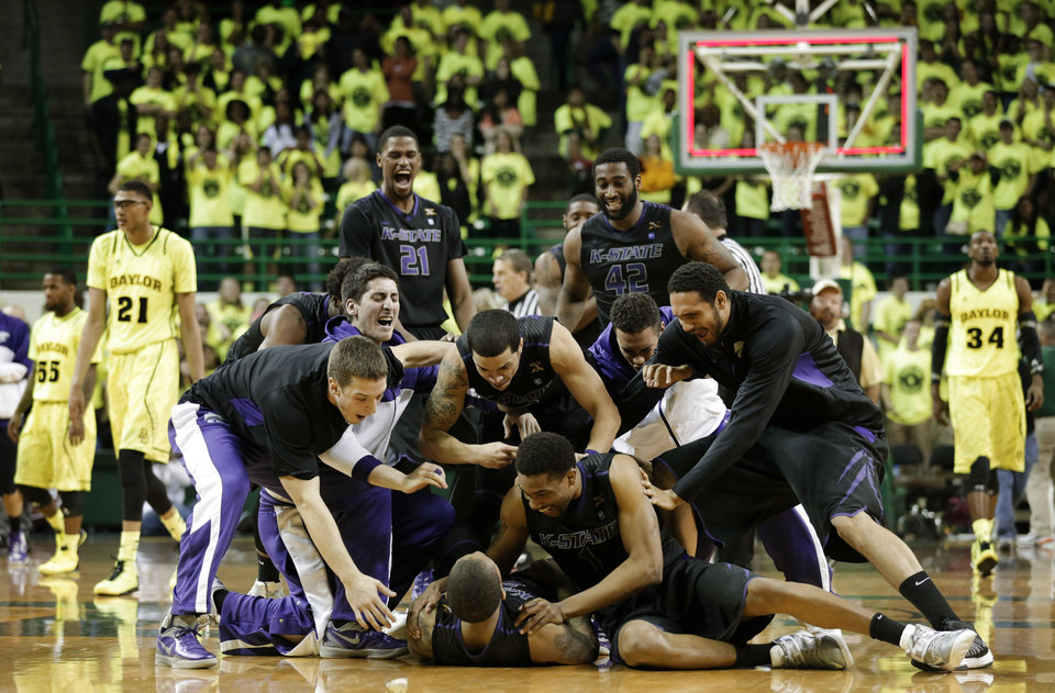 Kansas State players celebrate with Rodney McGruder, bottom, after he hit a final-second three-point basket to secure a 64-21 win against Baylor in an NCAA college basketball game on Saturday, March 2, 2013, in Waco, Texas. (AP Photo/Tony Gutierrez)