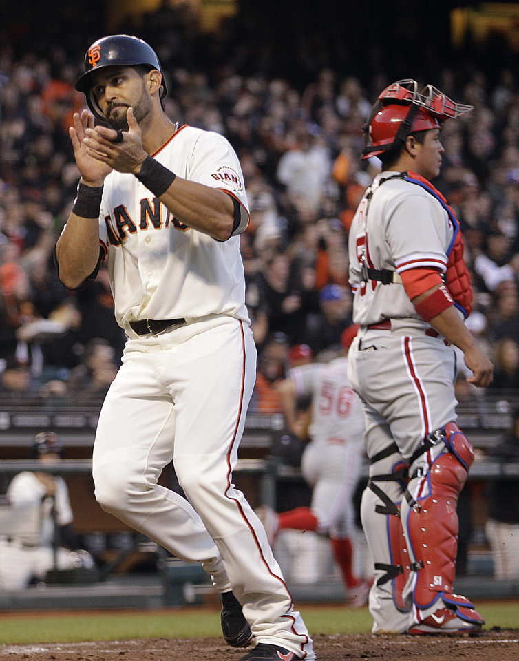 San Francisco Giants' Angel Pagan, left, celebrates as he scores behind Philadelphia Phillies catcher Carlos Ruiz during the first inning of a baseball game Tuesday, April 17, 2012, in San Francisco. Pagan scored on a triple by Melky Cabrera. (AP Photo/Ben Margot)