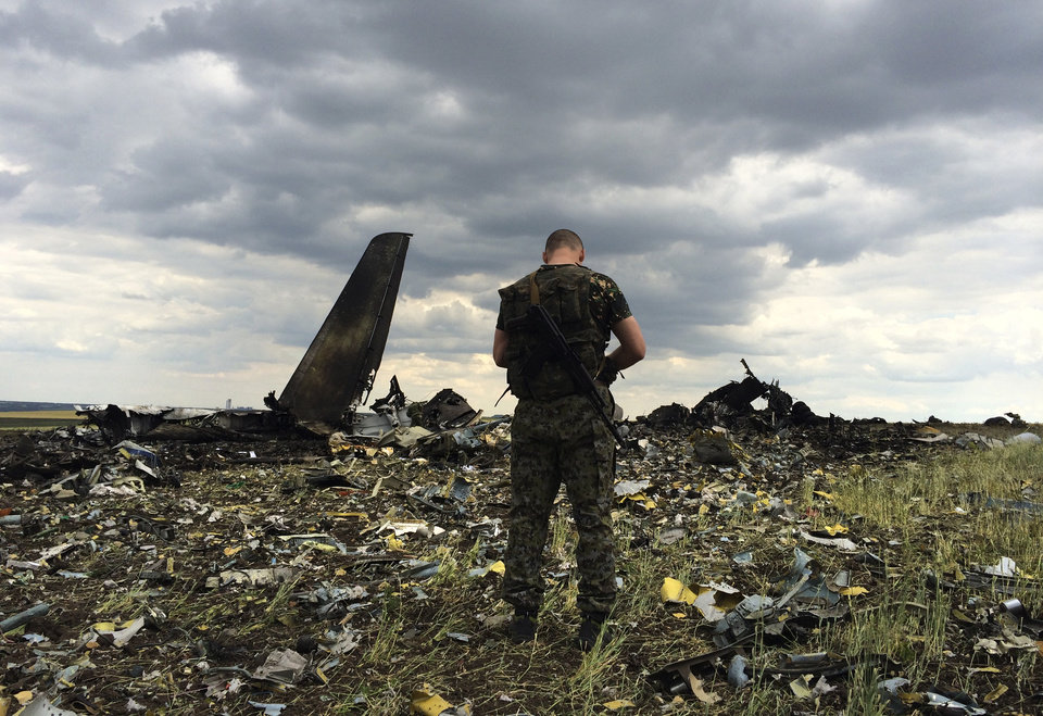 Photo - A pro-Russian fighter guards the site of remnants of a downed Ukrainian army aircraft Il-76 at the airport near Luhansk, Ukraine, Saturday, June 14, 2014. Pro-Russian separatists shot down the military transport plane Saturday in the country's restive east, killing all 49 service personnel on board, Ukrainian officials said. (AP Photo/Evgeniy Maloletka)