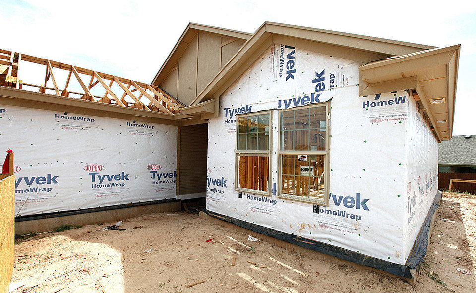 Photo - A house receiving its Tyvek wrap, a weather shield at 2612 NW 184. The specifics of how such products are to be installed depending on what siding material is to be applied ?hasn?t been covered? by codes until now, buillder-developer Todd Booze said. Booze is chairman of the planning committee for the Oklahoma Building Summit Sept. 18 in Midwest City.  PAUL B. SOUTHERLAND - The Oklahoman