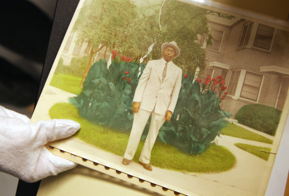 Photo - A photo archivist holds a tinted photograph on a table in the photo archive room at the Oklahoma History Center in January. The Center has hundreds of thousands of photographs and documents related to black history.  PAUL B. SOUTHERLAND - The Oklahoman