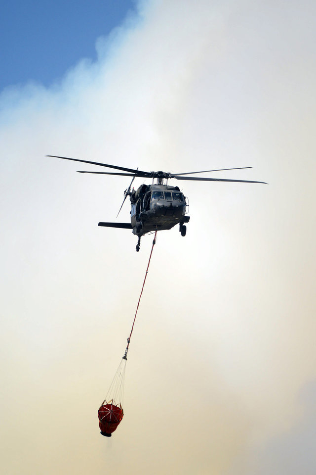 Photo - A helicopter from Ft. Carson's 4th Combat Aviation Brigade heads back for another load of water as the Black Forest Fire burns out of control for a second straight day near Colorado Springs, Colo. on Wednesday, June 12, 2013. Three Colorado wildfires fueled by hot temperatures, gusty winds and thick, bone-dry forests have together burned dozens of homes and led to the evacuation of more than 7,000 residents and nearly 1,000 inmates at medium-security prison. (AP Photo/Bryan Oller)
