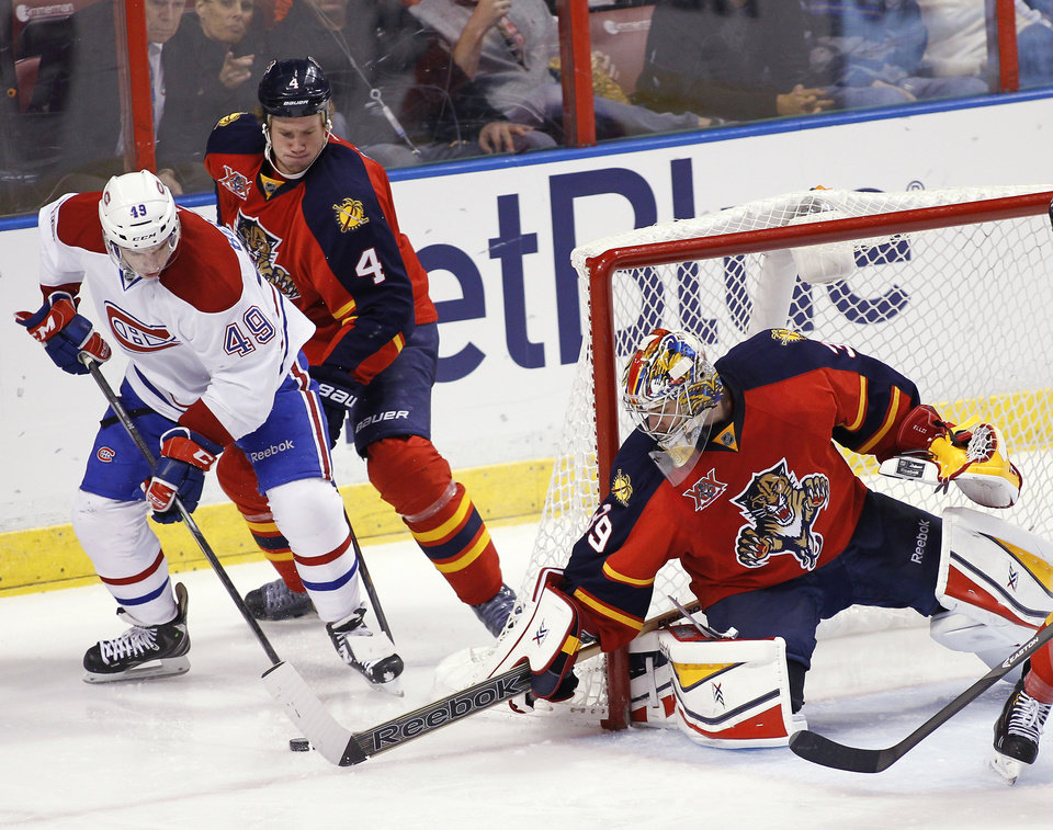 Photo - Montreal Canadiens left wing Michael Bournival (49) shoots as Florida Panthers' Dylan Olsen (4) and goalie Dan Ellis (39) defend during the second period of an NHL hockey game in Sunrise, Fla., on Saturday, March 29, 2014. (AP Photo/Terry Renna)
