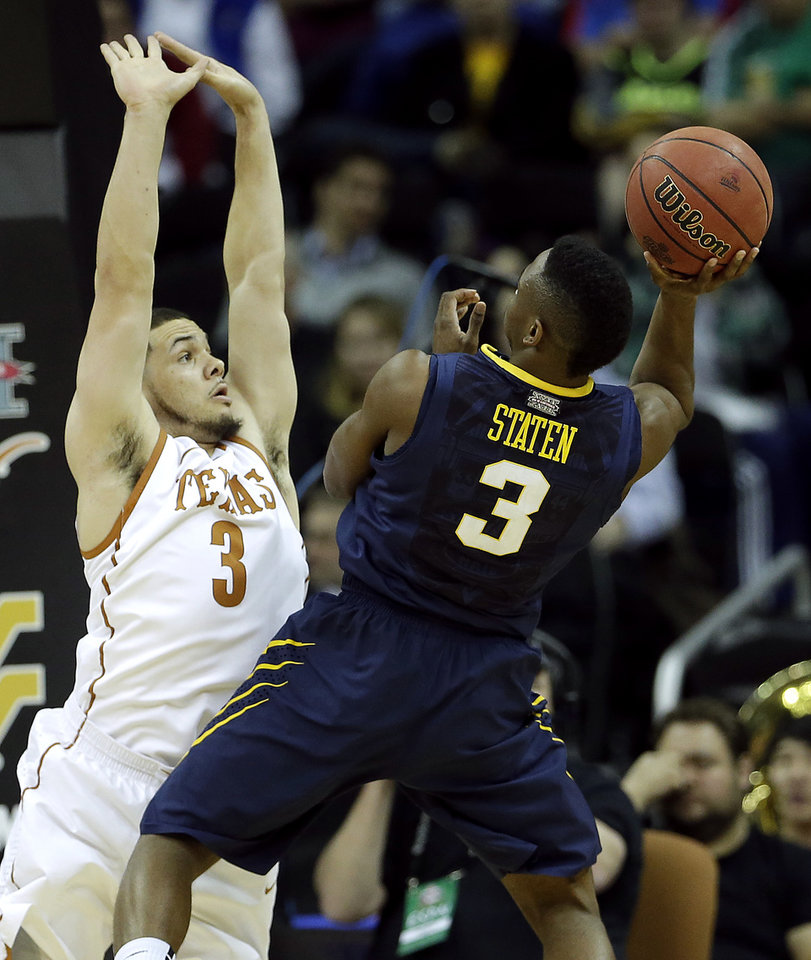 Photo - West Virginia's Juwan Staten, right, shoots under pressure from Texas' Javan Felix, left, during the first half of an NCAA college basketball game in the Big 12 men's tournament on Thursday, March 13, 2014, in Kansas City, Mo. (AP Photo/Charlie Riedel)