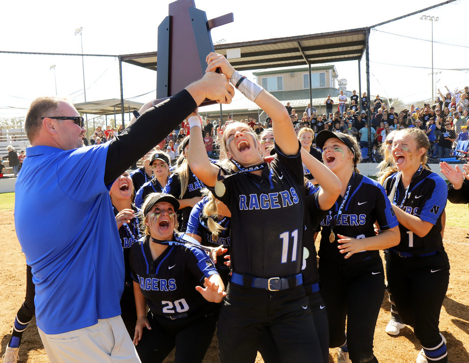 Photo - NHS #11 Maebree Robertson leaps for the trophy with the team behind her during the 4A Fast Pitch Championship game between Newcastle and Purcell at the Ball Fields at Firelake in Shawnee, Saturday, October 19, 2019. [Doug Hoke/The Oklahoman]