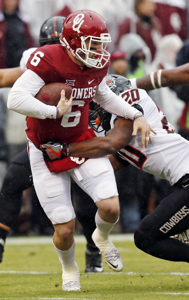 Photo - Oklahoma State's Jordan Burton (20) stops Oklahoma's Baker Mayfield (6) in the backfield in the first quarter during the Bedlam college football game between the Oklahoma Sooners (OU) and the Oklahoma State Cowboys (OSU) at Gaylord Family - Oklahoma Memorial Stadium in Norman, Okla., Saturday, Dec. 3, 2016. Photo by Nate Billings, The Oklahoman