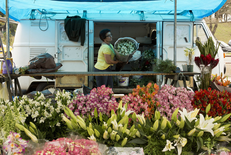 Photo - In this Sept. 3, 2013 photo, a vendor unloads a bouquet of flowers from her Volkswagen van, at a street market in Sao Paulo, Brazil. In Brazil the VW van is known as the