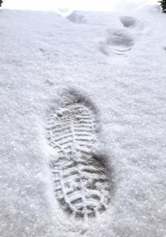 Photo -  Footprints left in the snow in Oklahoma City on Wednesday[Chris Landsberger/The Oklahoman]