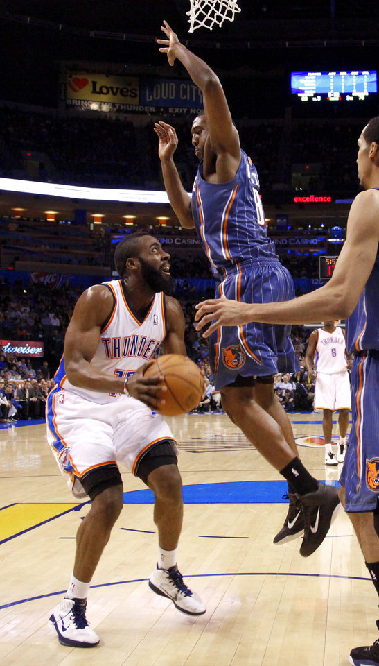 Oklahoma City's James Harden (13) looks up to the basket under Charlotte's D.J. White (8) during an NBA basketball game between the Oklahoma City Thunder and the Charlotte Bobcats at the Oklahoma City Arena, Friday, March 18, 2011. Photo by Bryan Terry, The Oklahoman