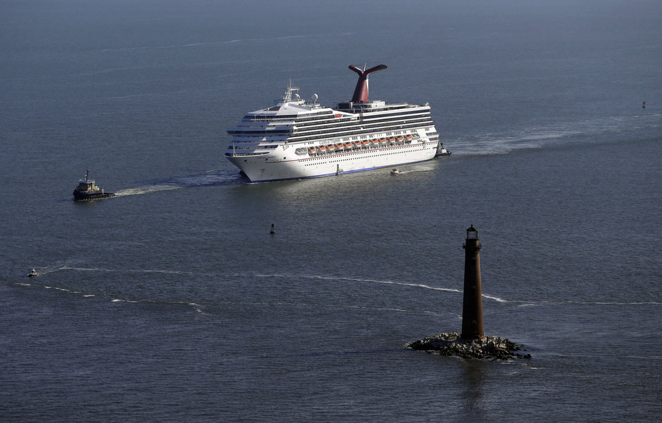 Photo - The disabled Carnival Lines cruise ship Triumph is towed to harbor off Mobile Bay, Ala., Thursday, Feb. 14, 2013. The ship with more than 4,200 passengers and crew members has been idled for nearly a week in the Gulf of Mexico following an engine room fire. (AP Photo/Gerald Herbert)