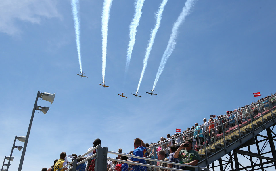 Photo - Fans look skyward during a flyover before the NASCAR Quicken Loans 400 auto race at Michigan International Speedway in Brooklyn, Mich., Sunday, June 15, 2014. (AP Photo/Bob Brodbeck)