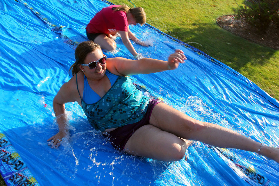 Photo - Freshmen Kady Turcotte and Alanna Grisham, both of Bartlesville, slide on a  water-soaked tarp during activities as University of Central Oklahoma students move on campus. PHOTO BY HUGH SCOTT, FOR THE OKLAHOMAN  HUGH SCOTT - FOR THE OKLAHOMAN