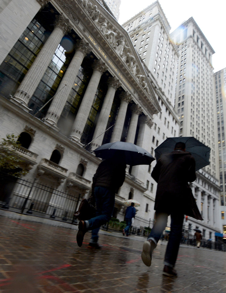 Photo -   Pedestrians walk in the rain past the New York Stock Exchange the day after Pres. Barack Obama was re-elected, Wednesday, Nov. 7, 2012 in New York. (AP Photo/Henny Ray Abrams)