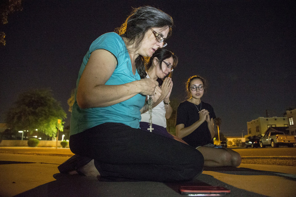 Photo - Mater Misericordiae (Mother of Mercy) Mission, church members, from left,  Mary Langlois,  Theresa Duarte, and Kirsten Duarte, prey as Phoenix Police investigate a shooting at the church on Wednesday, June 11, 2014 in Phoenix.  Police say one priest was shot to death and another is injured after an attack at the church in downtown Phoenix. The Roman Catholic Diocese of Phoenix on Thursday identified the slain priest as the Rev. Kenneth Walker and the injured priest as the Rev. Joseph Terra. (AP Photo/The Arizona Republic, Nick Oza)  MARICOPA COUNTY OUT; MAGS OUT; NO SALES