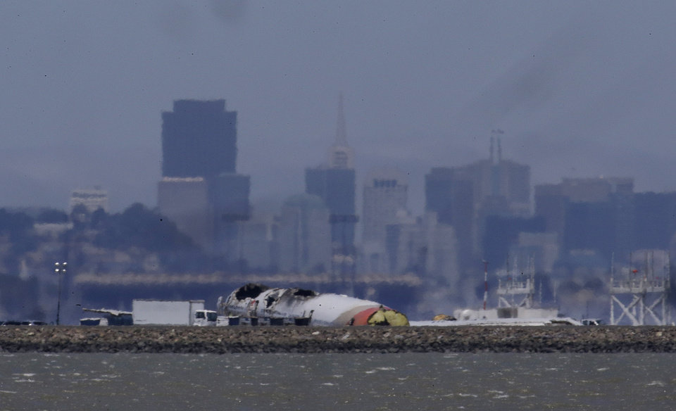 Photo - The wreckage of Asiana Flight 214, which crashed on Saturday, July 6, 2013, is seen on a tarmac in front of the San Francisco skyline at San Francisco International Airport in San Francisco, Wednesday, July 10, 2013. Investigators are struggling to piece together what went wrong in an accident that left two of the 307 aboard dead and close to 20 seriously injured.   (AP Photo/Jeff Chiu)