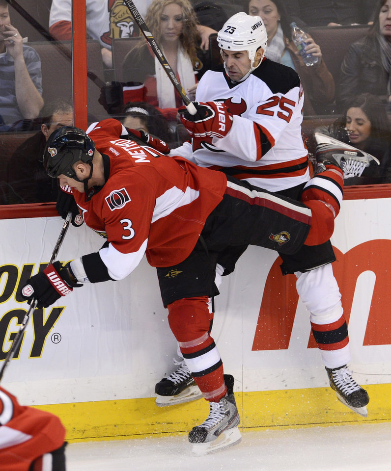 Photo - New Jersey Devils right wing Tom Kostopoulos collides with Ottawa Senators defenseman Marc Methot along the boards during second period NHL action in Ottawa, on Monday March 25, 2013. (AP Photo/The Canadian Press, Adrian Wyld)