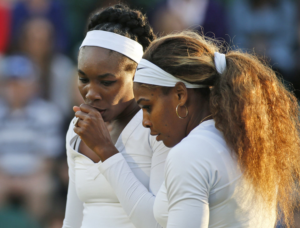 Photo - Serena Williams of the U.S., right, talks with her sister Venus Williams of the U.S., left, as they prepare to serve during a doubles match against Oksana Kalashnikova of Georgia and Olga Savchuk of Ukraine at the All England Lawn Tennis Championships in Wimbledon, London, Wednesday, June 25, 2014. (AP Photo/Alastair Grant)