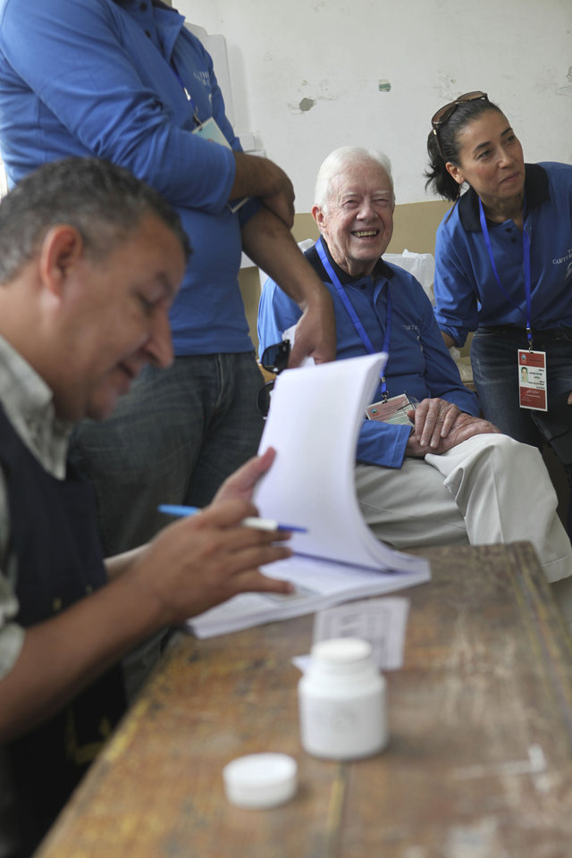 Photo -   Former U.S. President Jimmy Carter, center, observes the election process inside a polling station in the Sayeda Aisha neighborhood of Cairo, Egypt, Wednesday, May 23, 2012. The Carter Center is in Egypt to monitor the presidential elections. Egyptians went to the polls on Wednesday morning to elect a new president after the fall of ex-President Hosni Mubarak last year.(AP Photo/Thomas Hartwell)