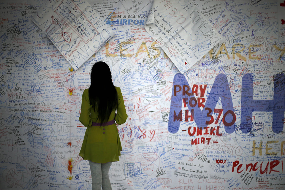 Photo - A woman reads messages and well wishes to people involved with the missing Malaysia Airlines jetliner MH370, Saturday, March 15, 2014 in Sepang, Malaysia. A Malaysian passenger jet missing for more than a week had its communications deliberately disabled and its last signal came about seven and a half hours after takeoff, meaning it could have ended up as far as Kazakhstan or deep in the southern Indian Ocean, Malaysia's Prime Minister Najib Razak said Saturday. (AP Photo/Wong Maye-E)