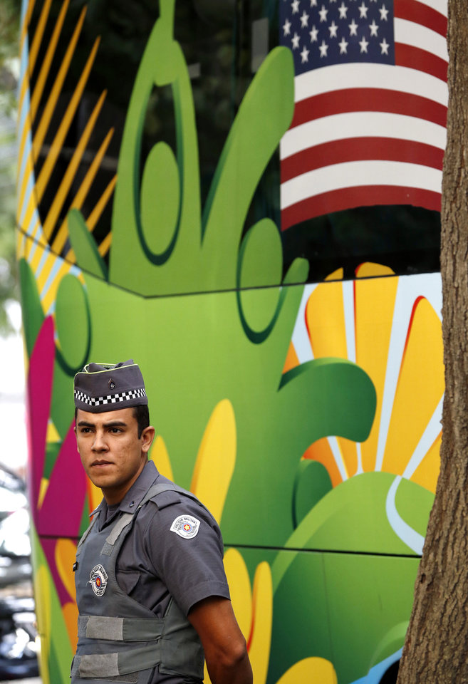 Photo - A police officer stands guard as the bus transporting members of the United States national soccer team, arrives at the team hotel in Sao Paulo, Brazil, Monday, June 9, 2014. The U.S. will play in group G of the 2014 soccer World Cup. (AP Photo/Julio Cortez)