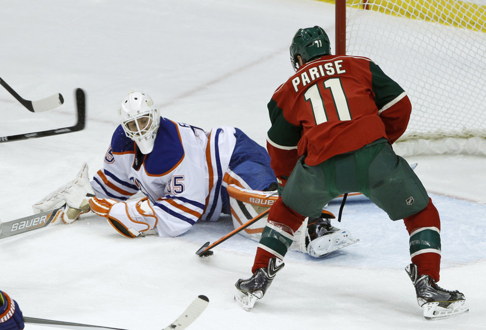 Photo - Minnesota Wild left wing Zach Parise (11) scores on Edmonton Oilers goalie Viktor Fasth, left, of Sweden, during the first period of an NHL hockey game in St. Paul, Minn., Tuesday, March 11, 2014. (AP Photo/Ann Heisenfelt)