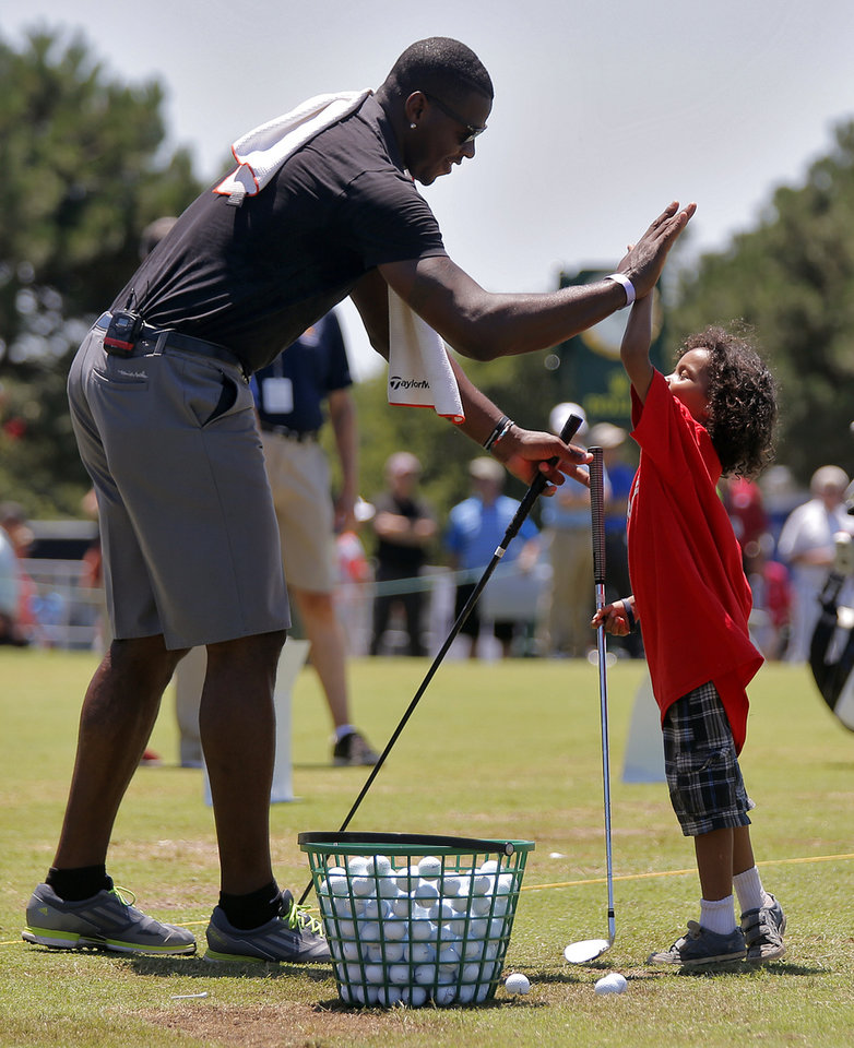 Photo - Desmond Mason give a high five to J.D. Turner during the Chevron Junior Day Exhibition at the U.S. Senior Open golf tournament at Oak Tree National in Edmond, Okla. on Wednesday, July 9, 2014. Photo by Chris Landsberger, The Oklahoman