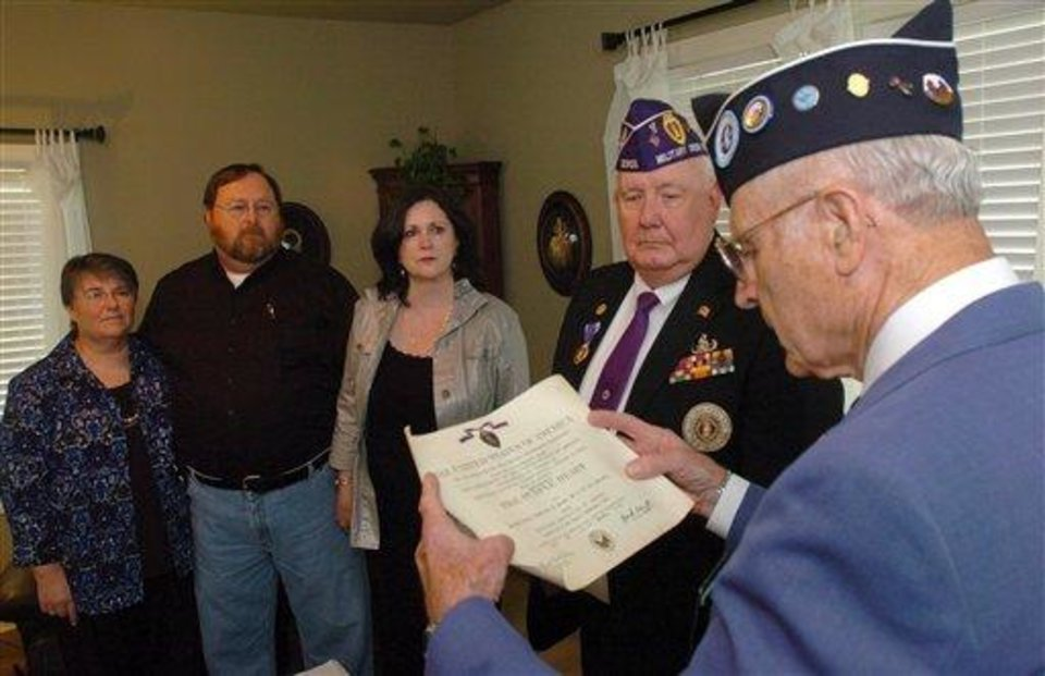 Grayson Tate reads a letter from then-president Harry Truman to Veer Krause on his receiving the Purple Heart during the Korean War during a ceremony in the family house in Gurley, Ala. Krause, a Korean War veteran, had his Purple Heart bought for a dollar at a garage sale in Illinois is being returned to a Gurley relative almost 60 years after he died in battle. It was returned to the family during a quiet family ceremony in Gurley. (AP Photo/The Huntsville Times, Eric Schultz)