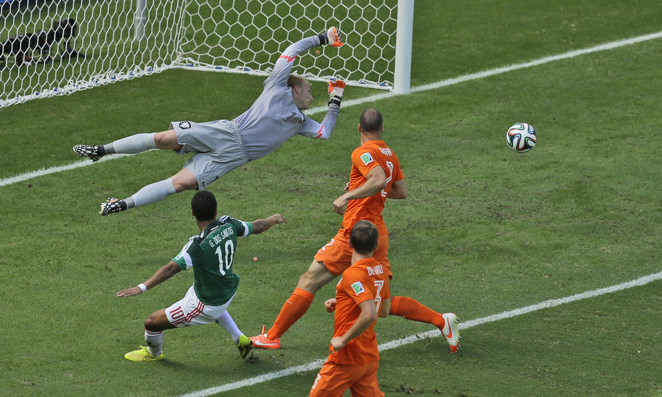 Photo - Mexico's Giovani dos Santos, left, shoots past the goal of Netherlands' goalkeeper Jasper Cillessen, back, during the World Cup round of 16 soccer match between the Netherlands and Mexico at the Arena Castelao in Fortaleza, Brazil, Sunday, June 29, 2014. (AP Photo/Themba Hadebe)