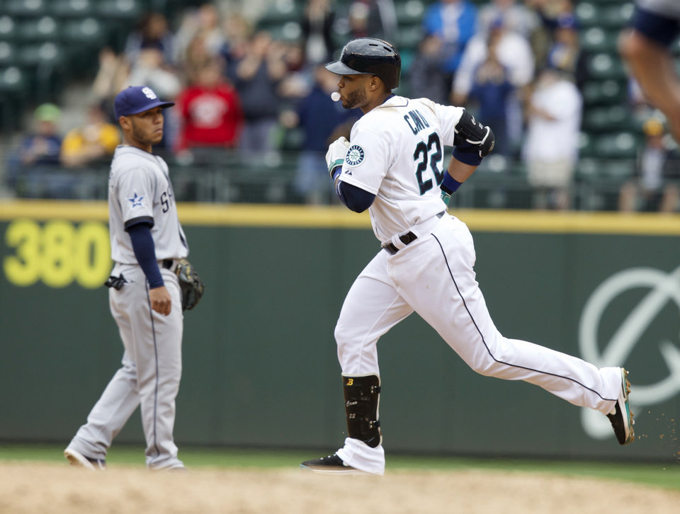 Photo - Seattle Mariners' Robinson Cano, right, blows a bubble as he rounds the bases after hitting a two-run home run during the fifth inning of a baseball game against the San Diego Padres in Seattle, Tuesday, June 17, 2014. At left is Padres third baseman Alexi Amarista. (AP Photo/Stephen Brashear)