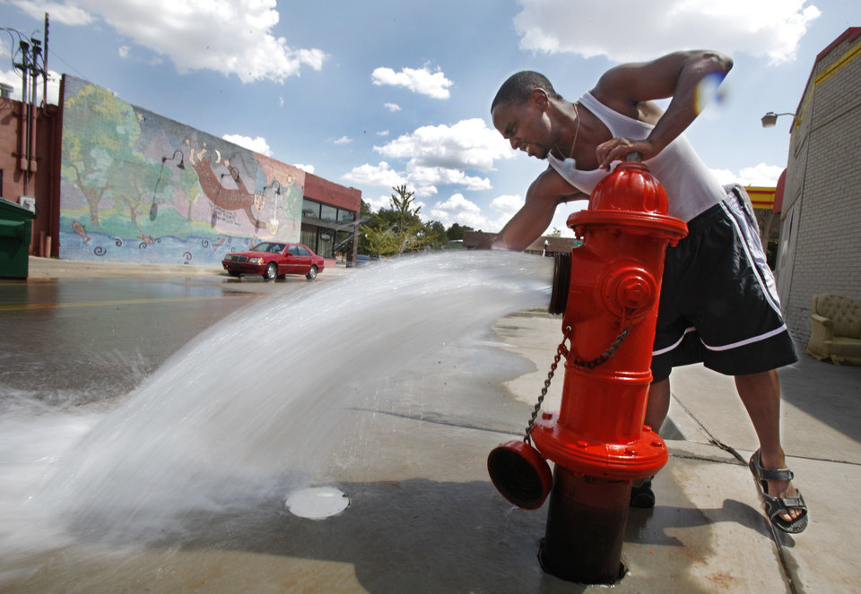 Kevin Adams fills a bottle with water from an open fire hydrant near NW 16 and Gatewood Avenue in Oklahoma City, August July 01, 2011. Photo by Steve Gooch