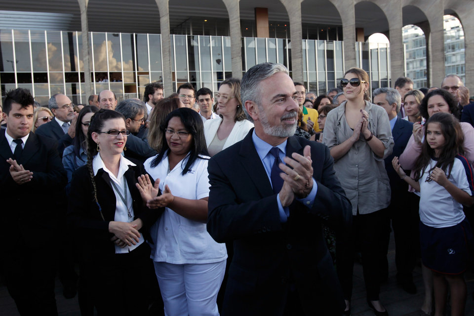 Photo - Brazil's Foreign Minister Antonio de Aguiar Patriota, center, applauds with workers outside the Itamaraty Palace, where the foreign ministry has their headquarters, as they surround the building to give it a symbolic hug after being damaged by protesters the previous night in Brasilia, Brazil, Friday, June 21, 2013. Protesters have expressed frustration with corruption and what they say are high taxes and poor public services. (AP Photo/Eraldo Peres)