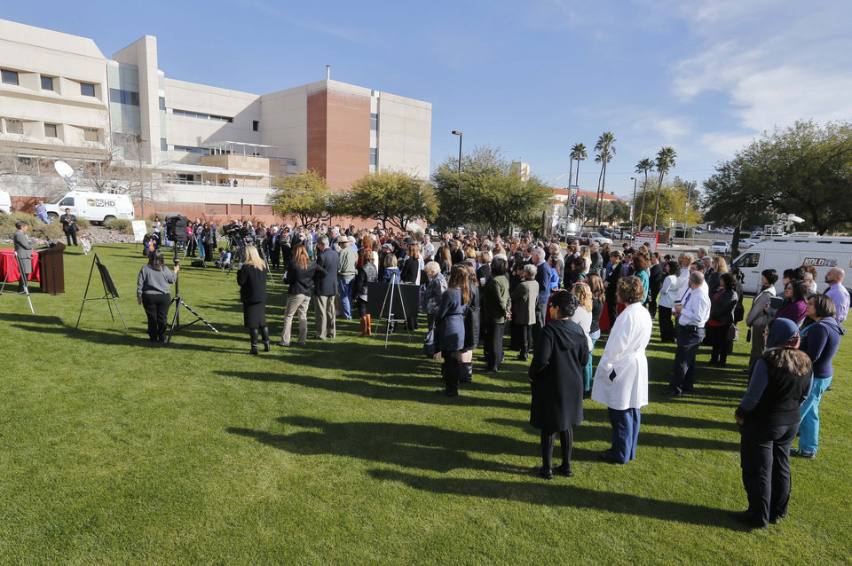 Photo - People assemble on the lawn outside University of Arizona Medical Center during a remembrance ceremony on the third anniversary of the Tucson shootings, Wednesday, Jan. 8, 2014, in Tucson, Ariz. Six people were killed and 13 wounded, including U.S. Rep. Gabrielle Giffords, D-Ariz., in the shooting rampage at a community event hosted by Giffords. The victims were all transported to the medical center in 2011. (AP Photo/Matt York)